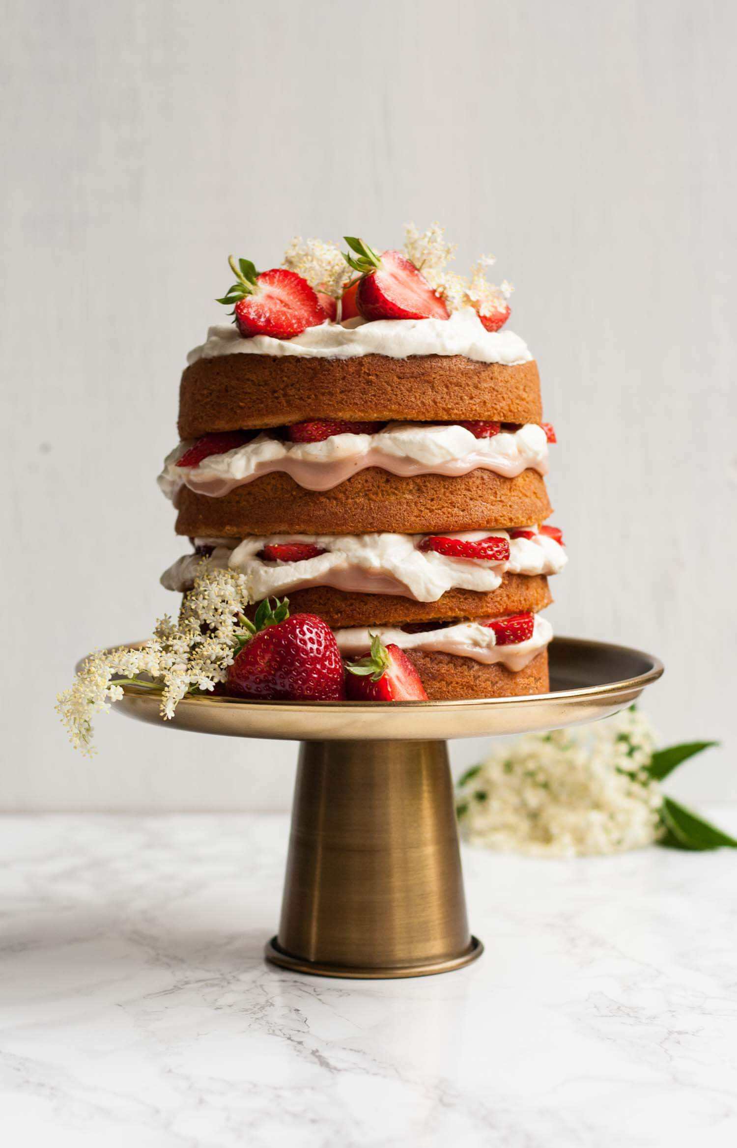 Strawberry and Elderflower Curd Layer Cake - this impressive layer cake is filled with the flavours of summer and is surprisingly easy to make! | eatloveeats.com