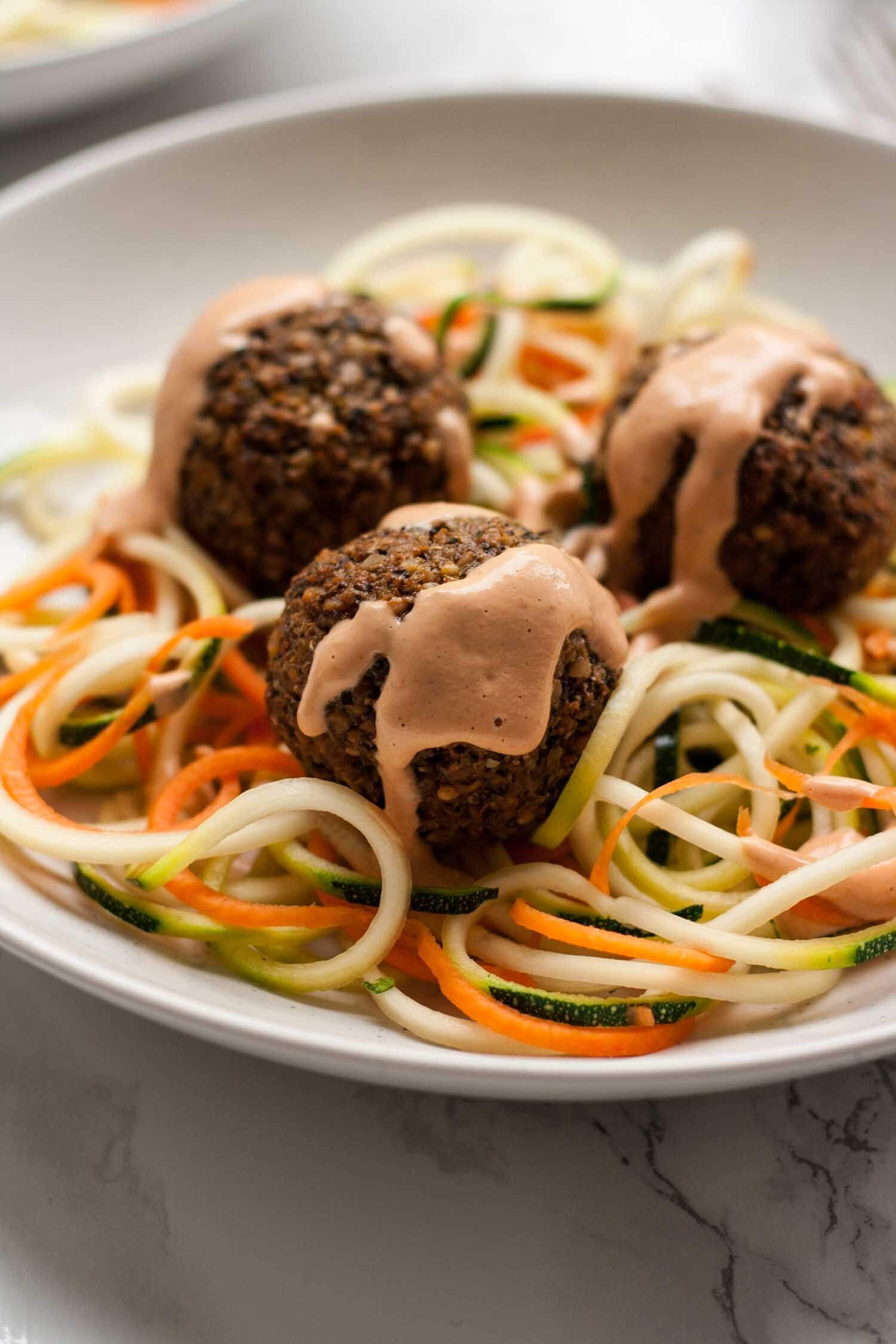 Vegan Meatballs with Creamy Sun-dried Tomato Sauce - these deliciously satisfying vegan meatballs make a perfect packed lunch served with spiralized veggies and a simple vegan sauce! | eatloveeats.com