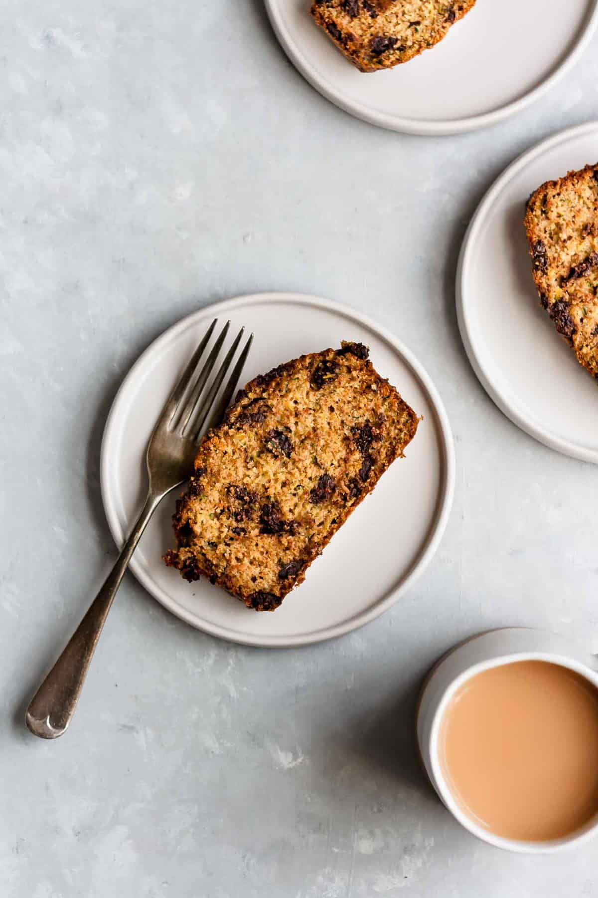 Slices of zucchini bread on plates with a fork and a mug of tea