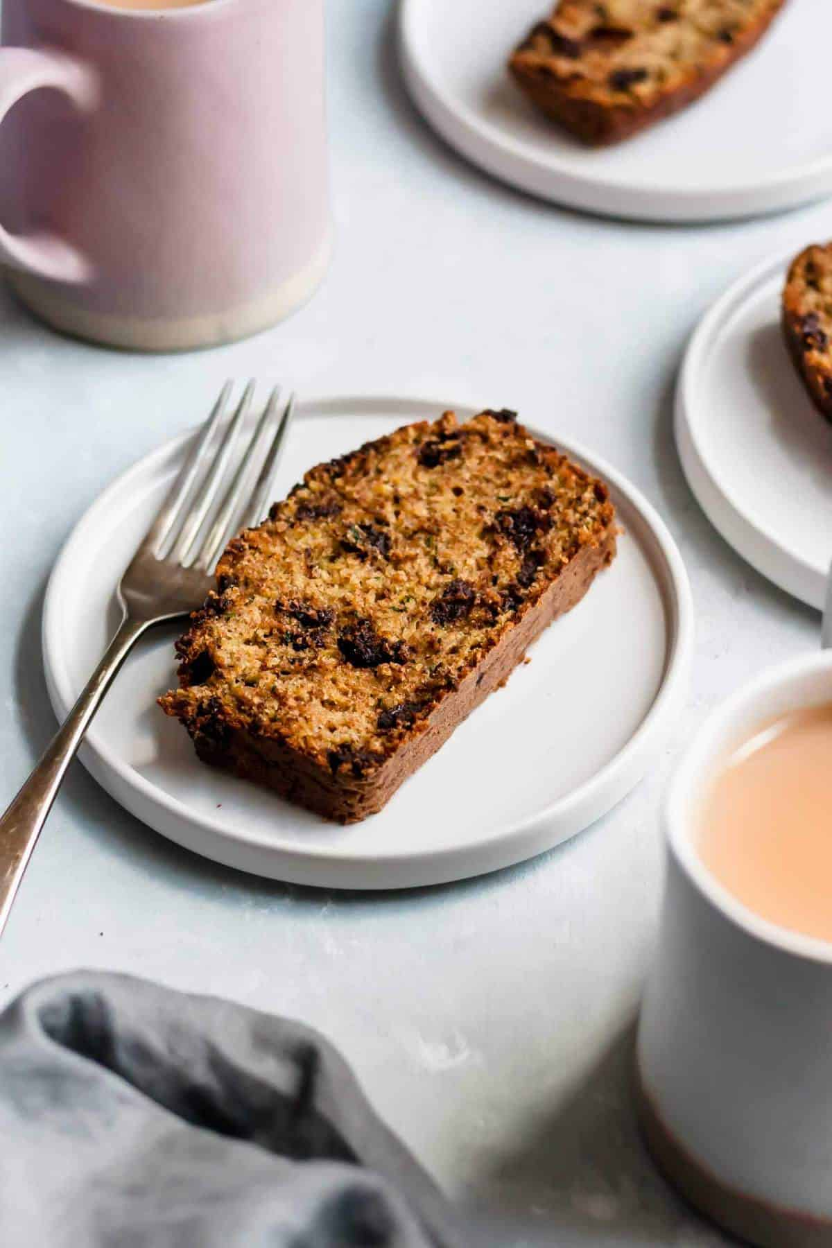 a slice of zucchini bread on a plate with a fork and a mug of tea nearby