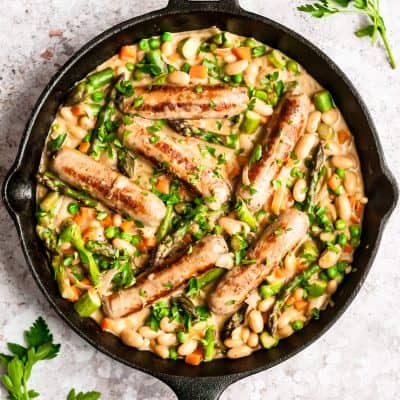 shot of finished dish of creamy chicken sausages and vegetables in a cast iron skillet