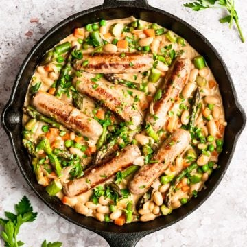 shot of finished dish of creamy turkey sausages and vegetables in a cast iron skillet