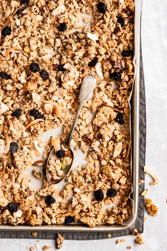 baking sheet with coconut tahini pistachio granola and a spoon