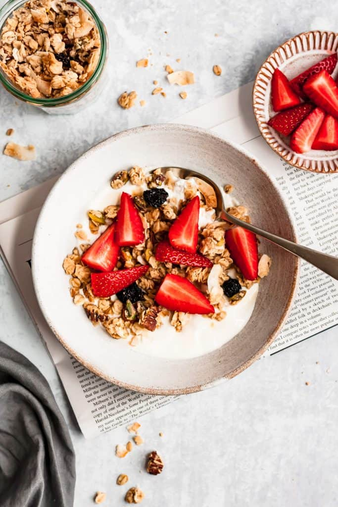 coconut tahini pistachio granola in a bowl with yoghurt and strawberries with a spoon and granola scattered around