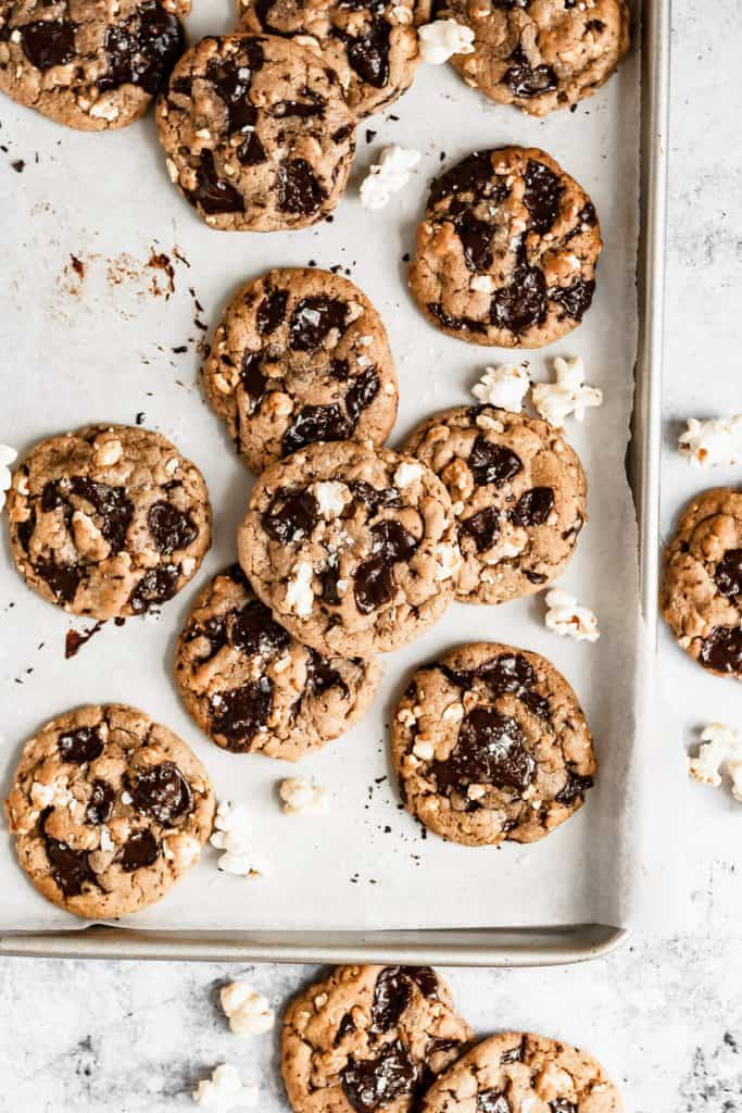a sheet pan with lots of popcorn chocolate chip cookies and popcorn scattered around