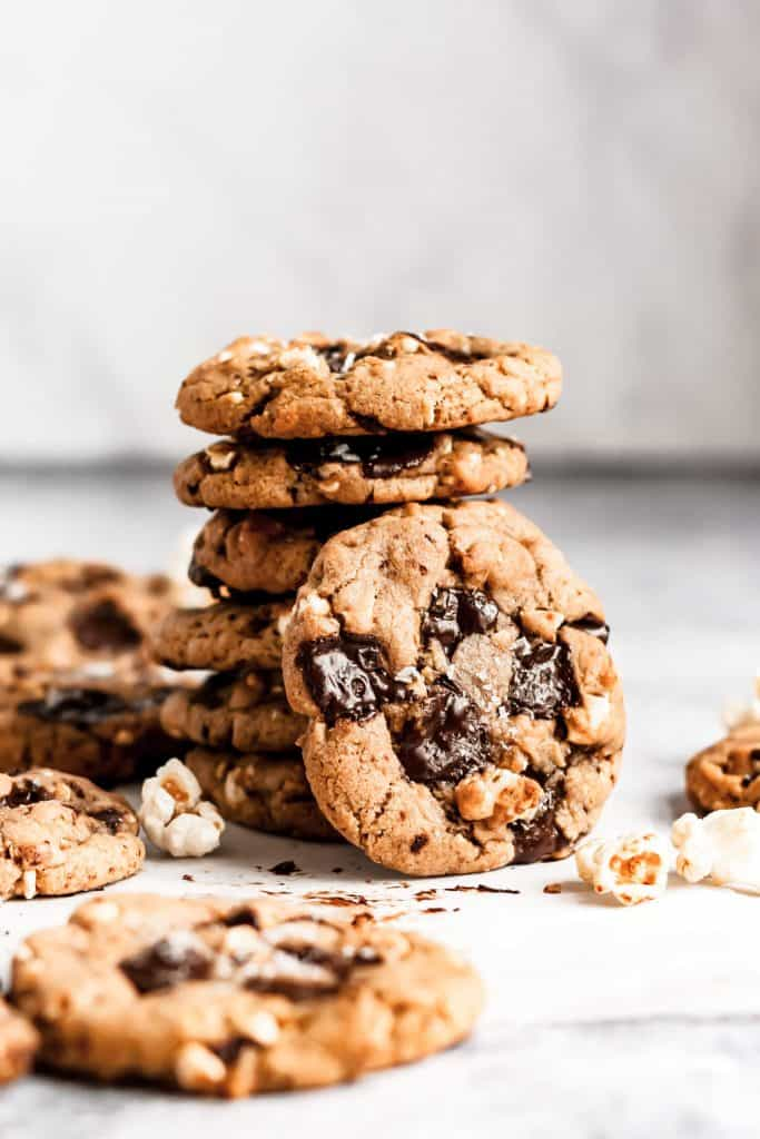 a stack of popcorn chocolate chip cookies with one cookie leaning against the stack and popcorn scattered around