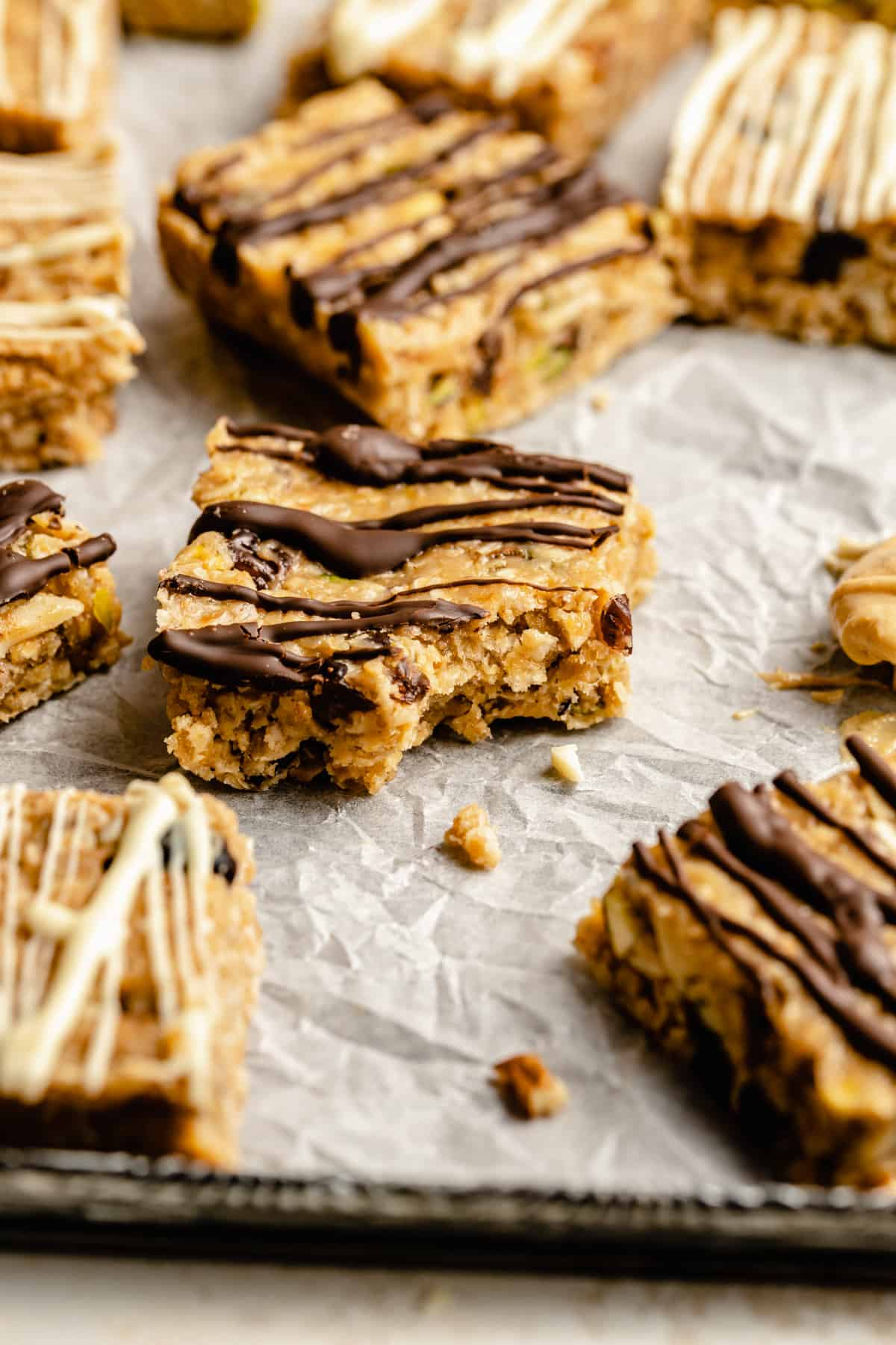 granola bars drizzled with chocolate on a piece of crumpled parchment paper