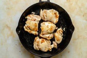 Chicken thighs sauteing in a skillet