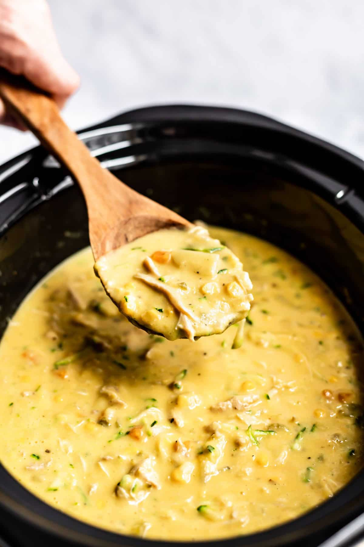 a wooden spoon lifting out some chowder from a slow cooker bowl
