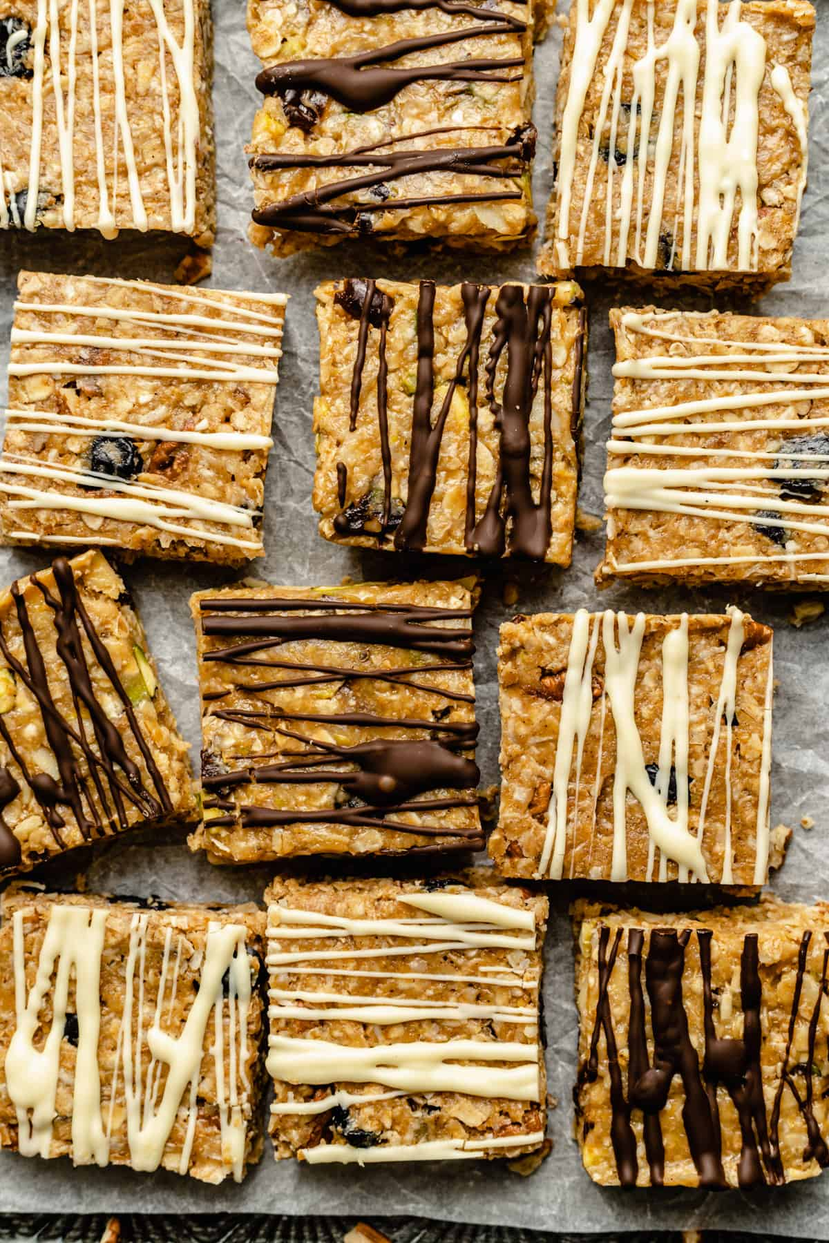 a granola bar with a bite taken out stacked on top of another bar, with more granola bars in the background