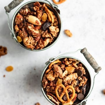 Two small metal buckets filled with maple almond butter snack mix and some pieces scattered around