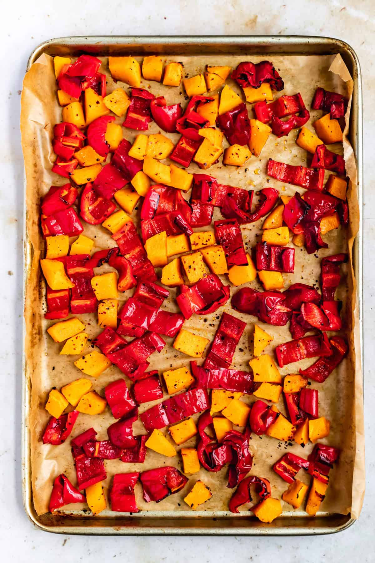a baking sheet lined with parchment paper, with roasted squash and red peppers