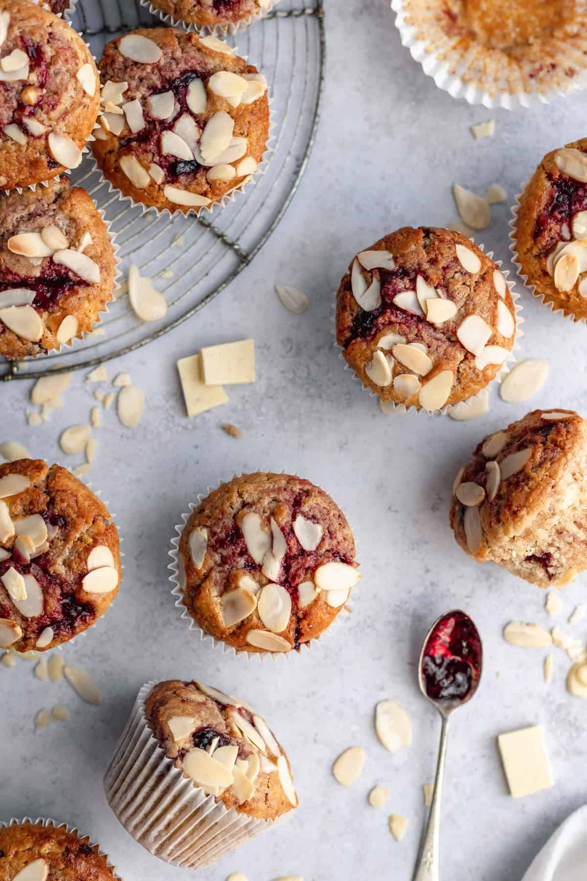 image shows a cooling rack, several muffins with flaked almonds on top and some almonds and white chocolate scattered around