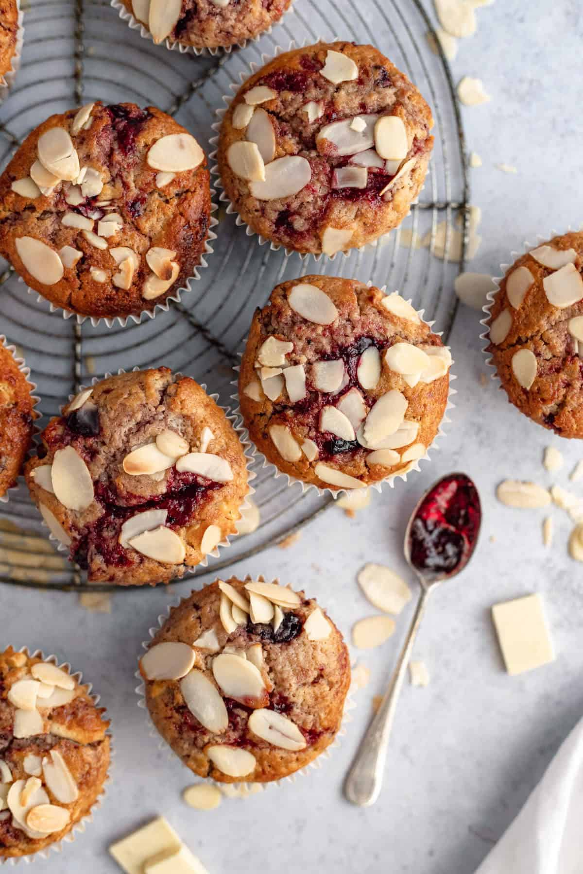 a few sourdough muffins on a cooling rack, a spoon with jam on it and some almonds and white chocolate scattered around