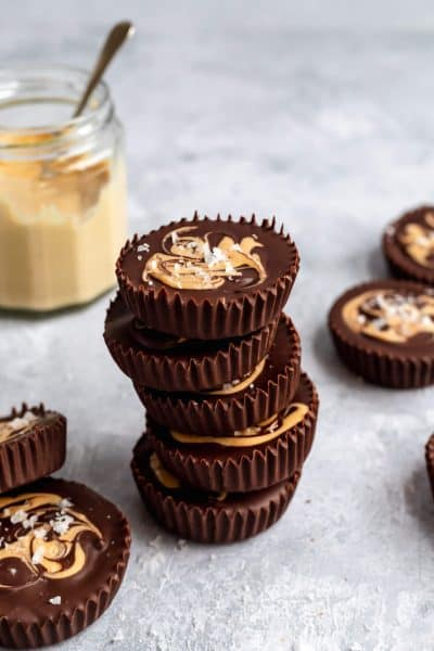 stack of cashew butter cups with a jar of cashew butter in the background