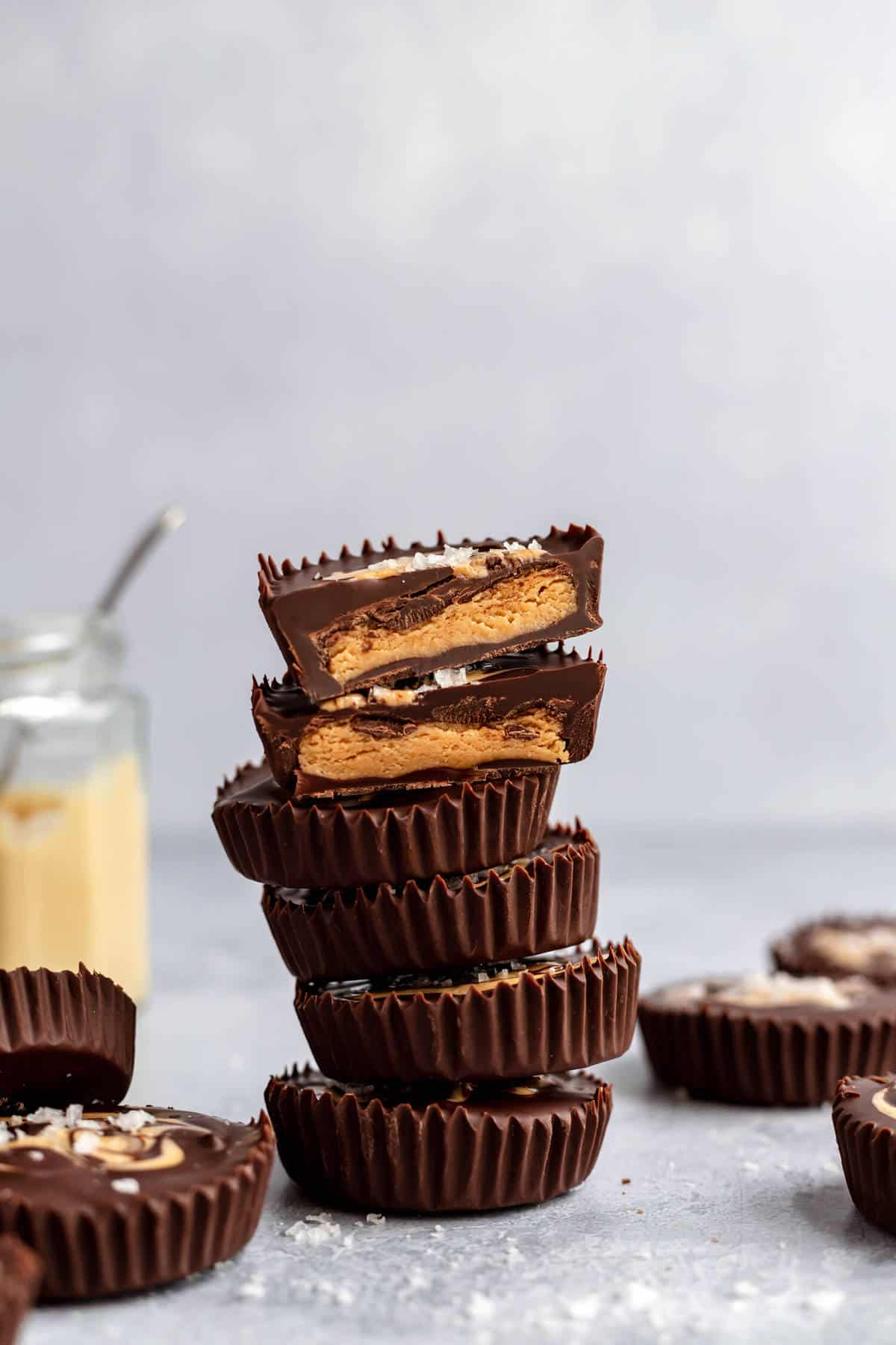 a stack of cashew butter cups with one cut in half to show the inside