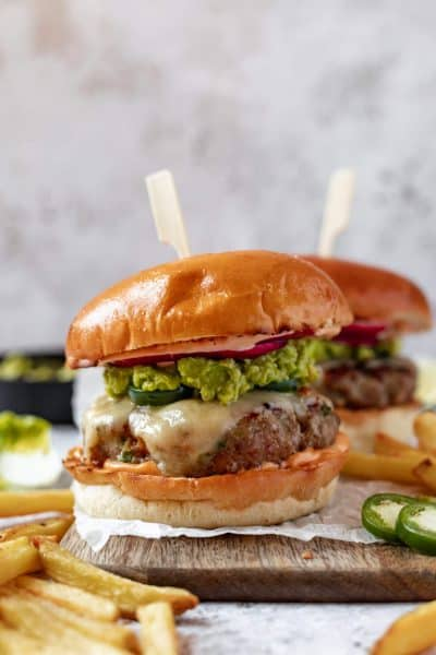 a close up of a burger on a wooden board covered in melted cheese and smashed avocado with a skewer in the top
