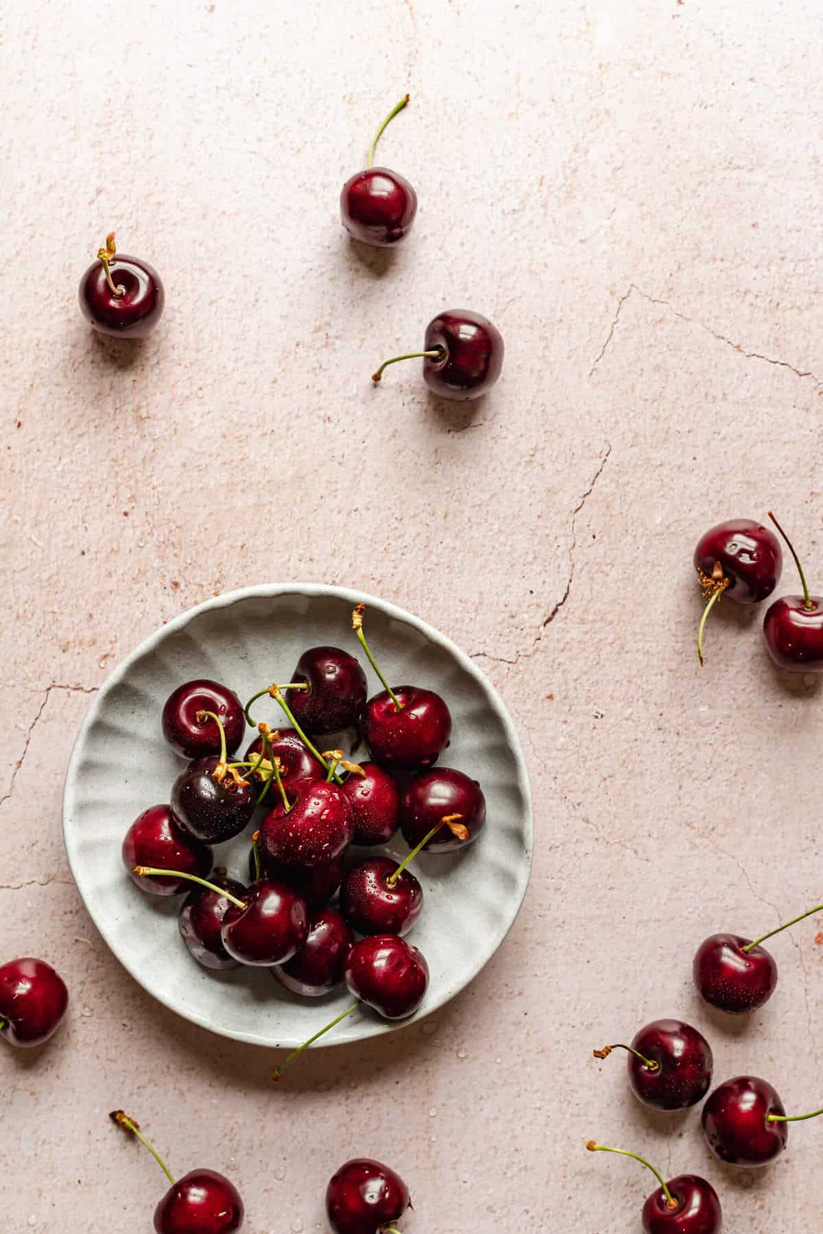 a small dish of cherries with a few more cherries scattered around