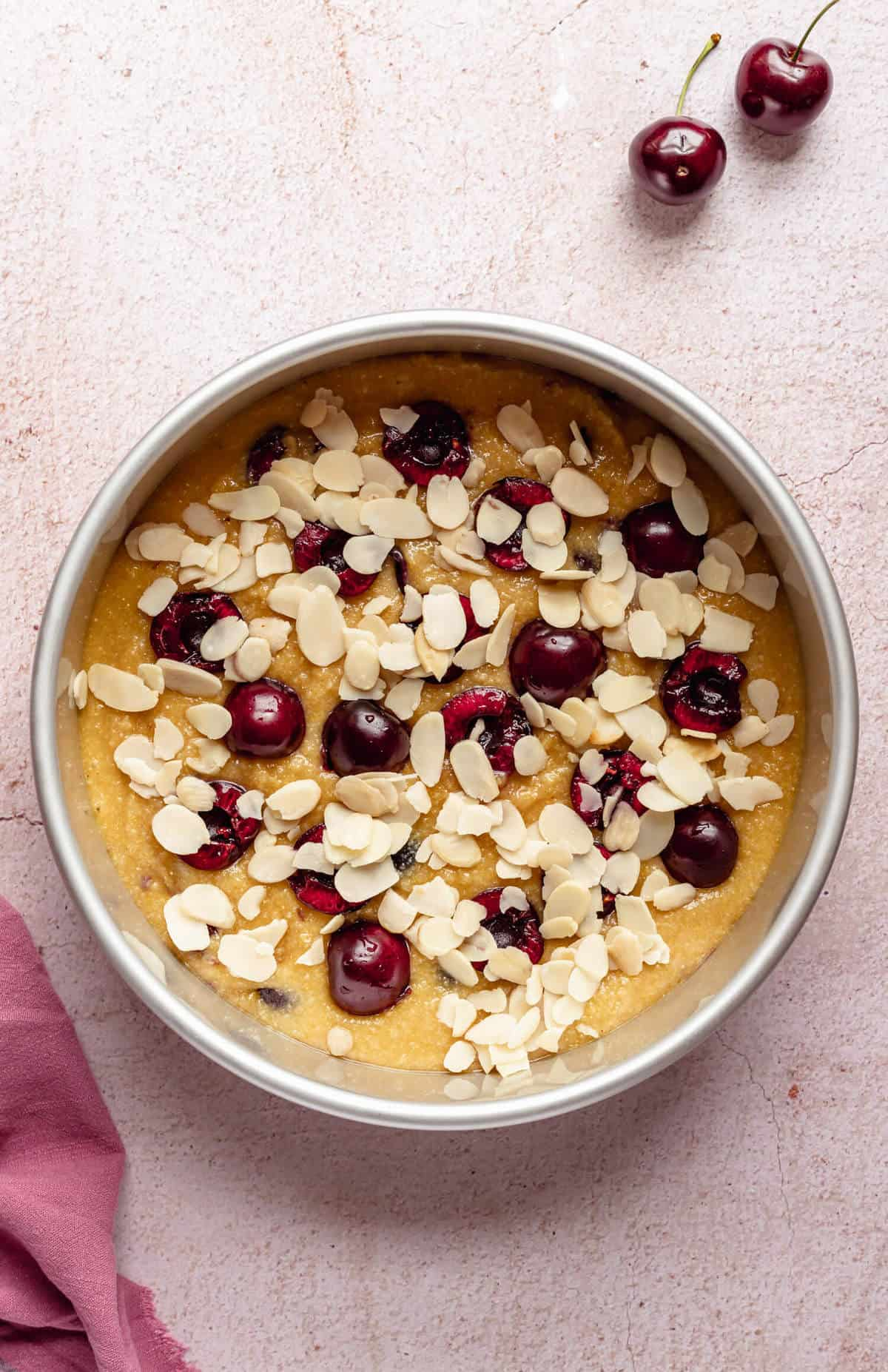 a cake tin filled with unbaked cake batter and topped with halved cherries and flaked almonds