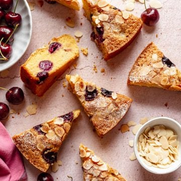 several slices of cake arranged on a peach plaster background, with a small bowl of flaked almonds and cherries