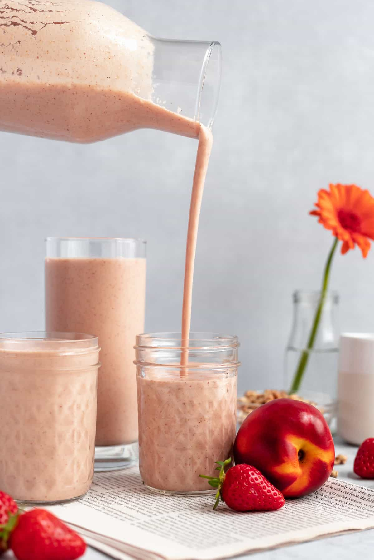 a smoothie being poured from a bottle into a jar, a couple of glasses of smoothie and a flower in the background
