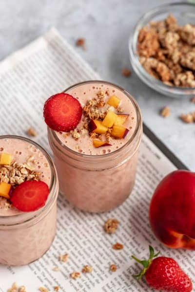 a pink smoothie in a jar on top of a newspaper, with a bowl of granola in the background
