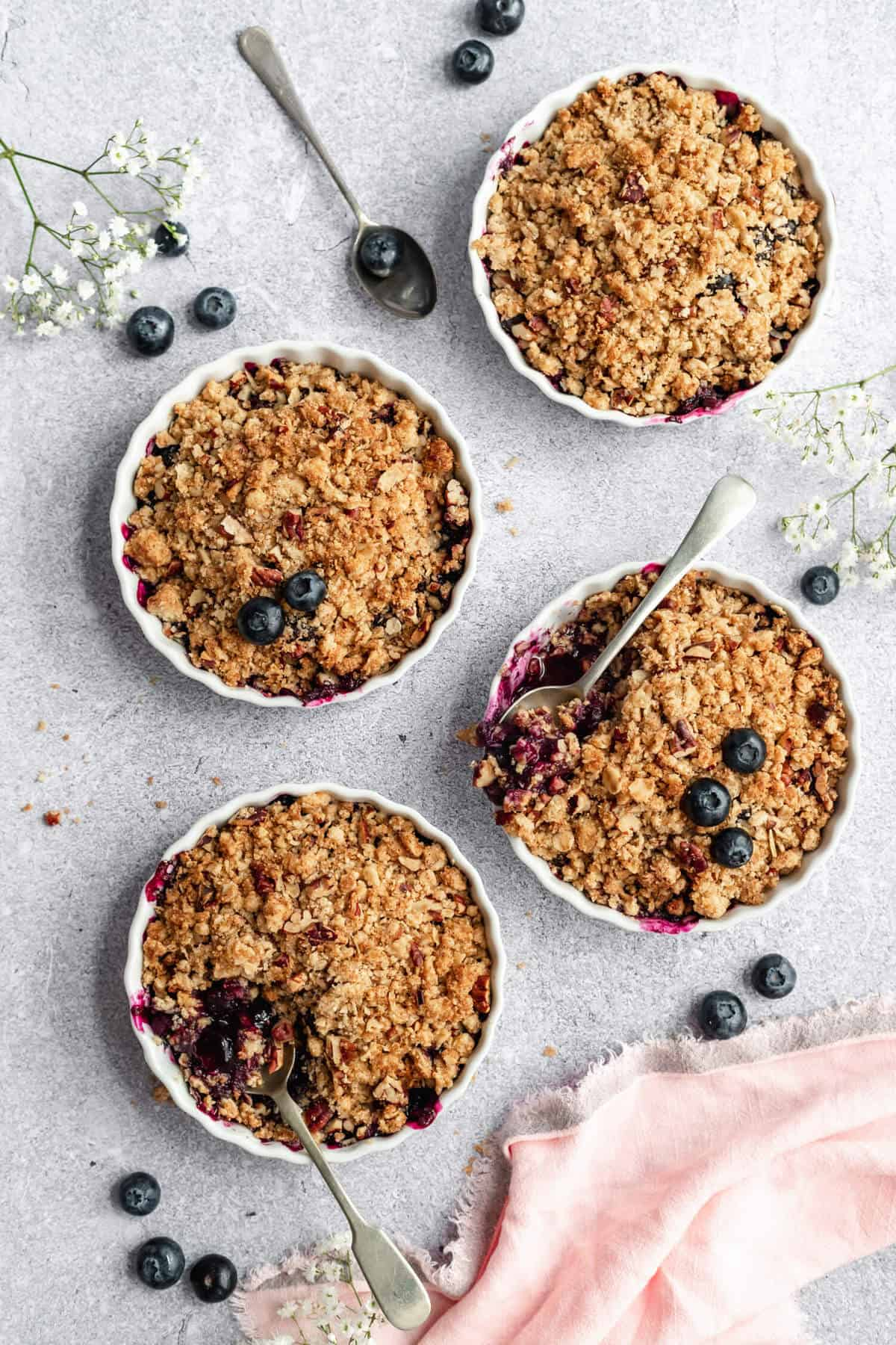 four ramekins filled with fruit crisp with spoons digging in and blueberries scattered around