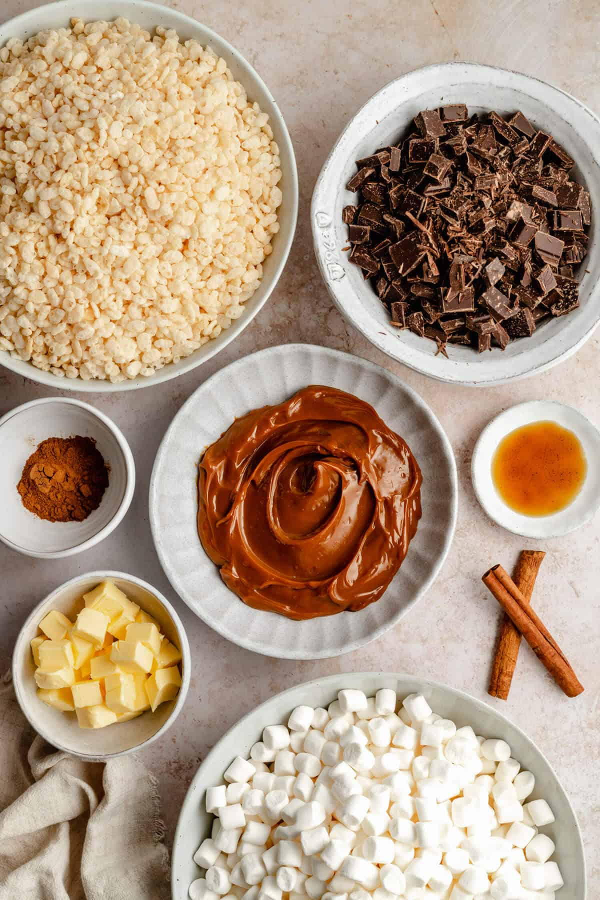 Various bowls of ingredients photo, rice krispies, chopped chocolate, ground cinnamon, dulce de leche, vanilla extract, butter, marshmallows