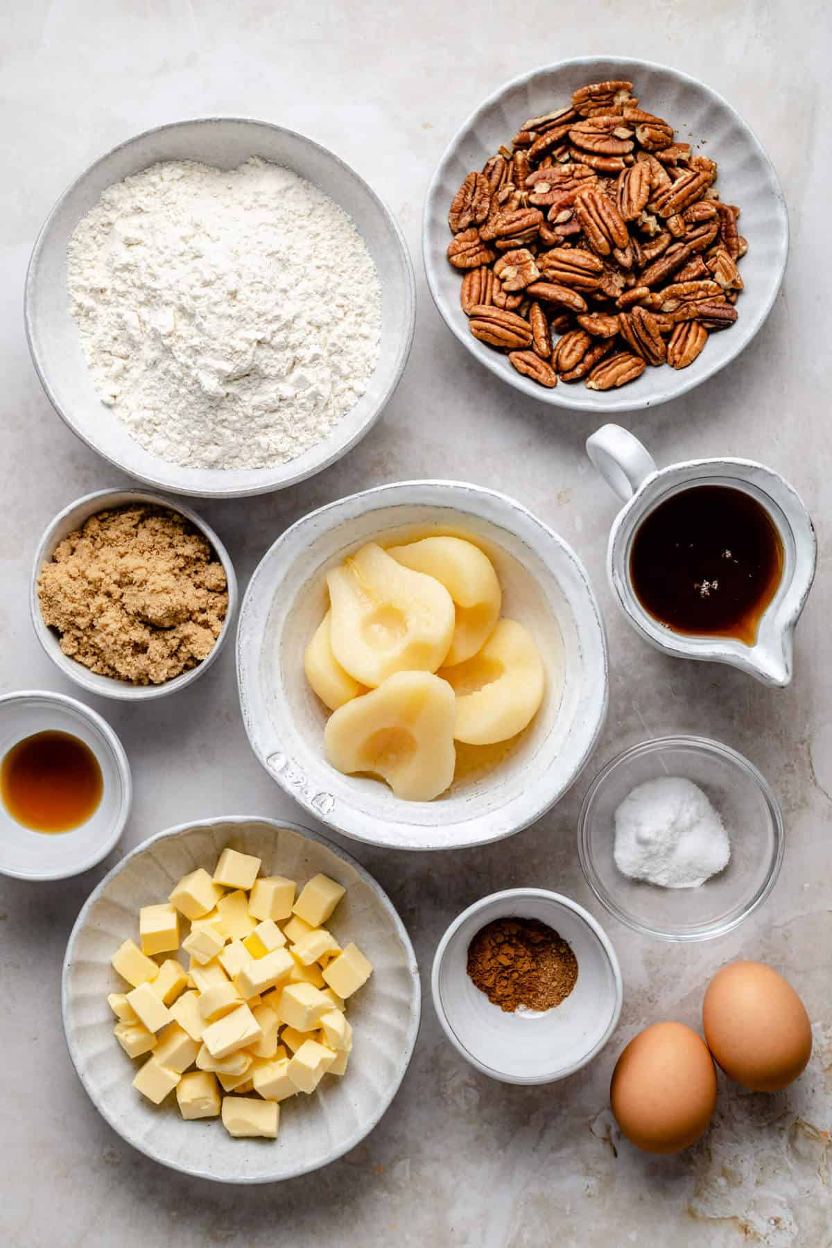 photo of various bowls containing the ingredients from the recipe, including canned pears, pecans, flour, butter and maple syrup