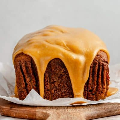 Photo of the glazed pumpkin gingerbread loaf with the glaze pouring over the side