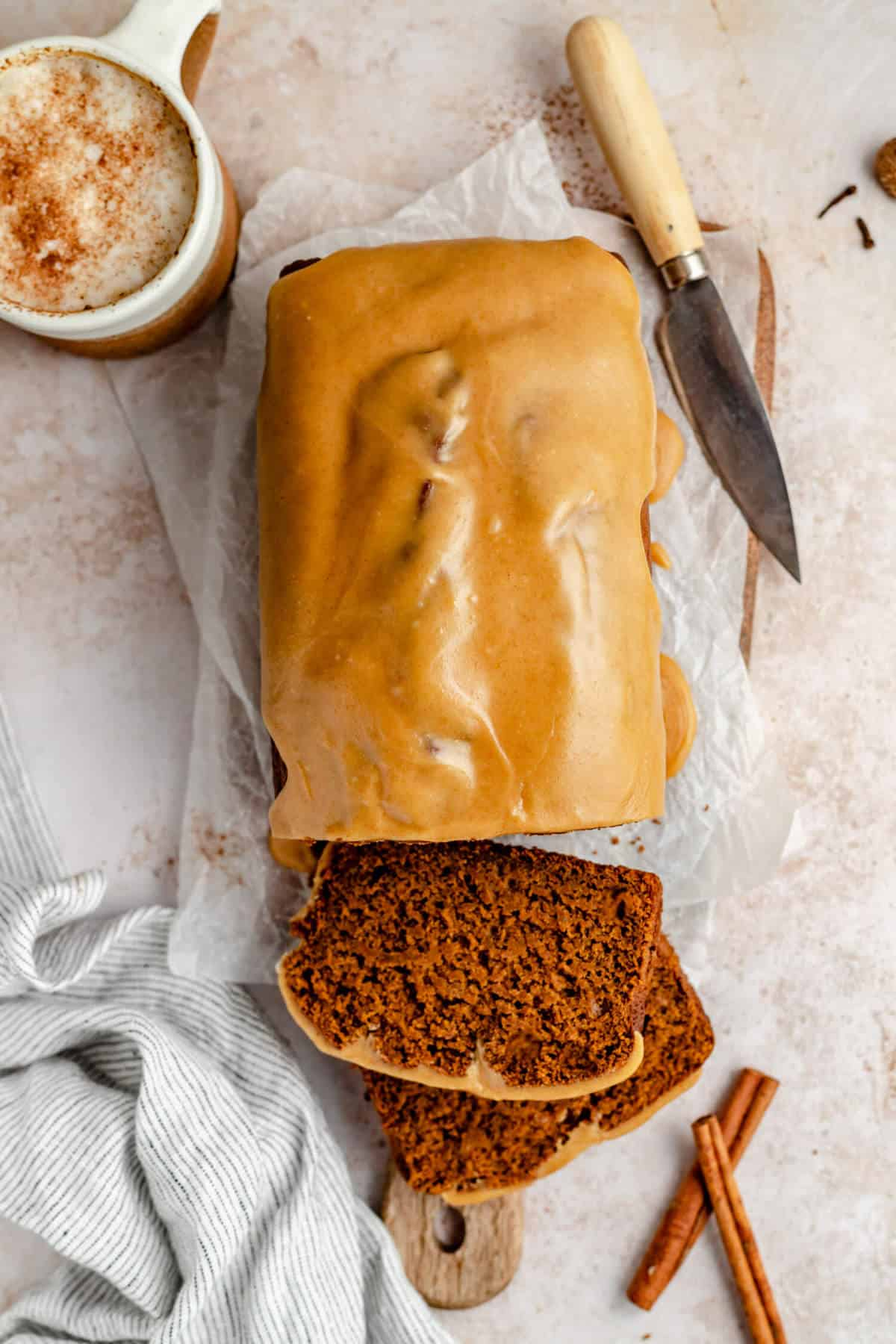 overhead photo of the glazed pumpkin gingerbread sliced on a board with a knife and cappuccino