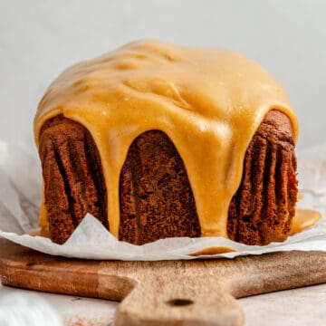 Pumpkin gingerbread side on with brown butter caramel glaze drizzling down the sides on a chopping board with parchment paper.