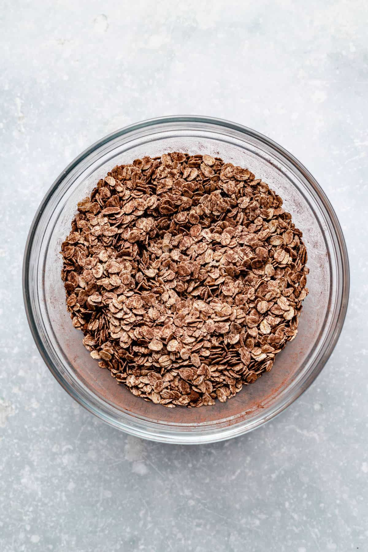 a glass mixing bowl containing rolled oats tossed with cocoa powder