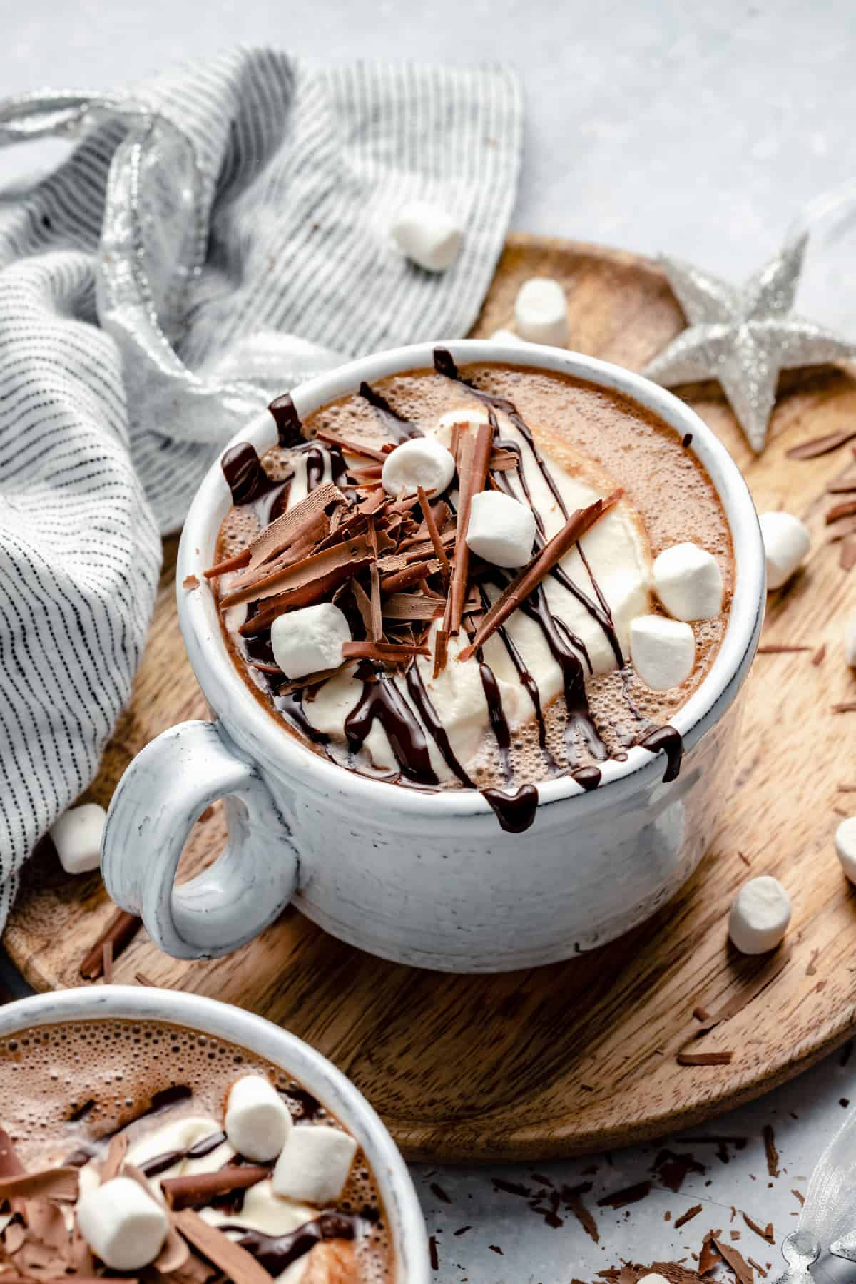 a mug of frothy peppermint ganache hot chocolate topped with whipped cream, marshmallows and melted and shaved chocolate, on top of a wooden board and surrounded with silver christmas decorations