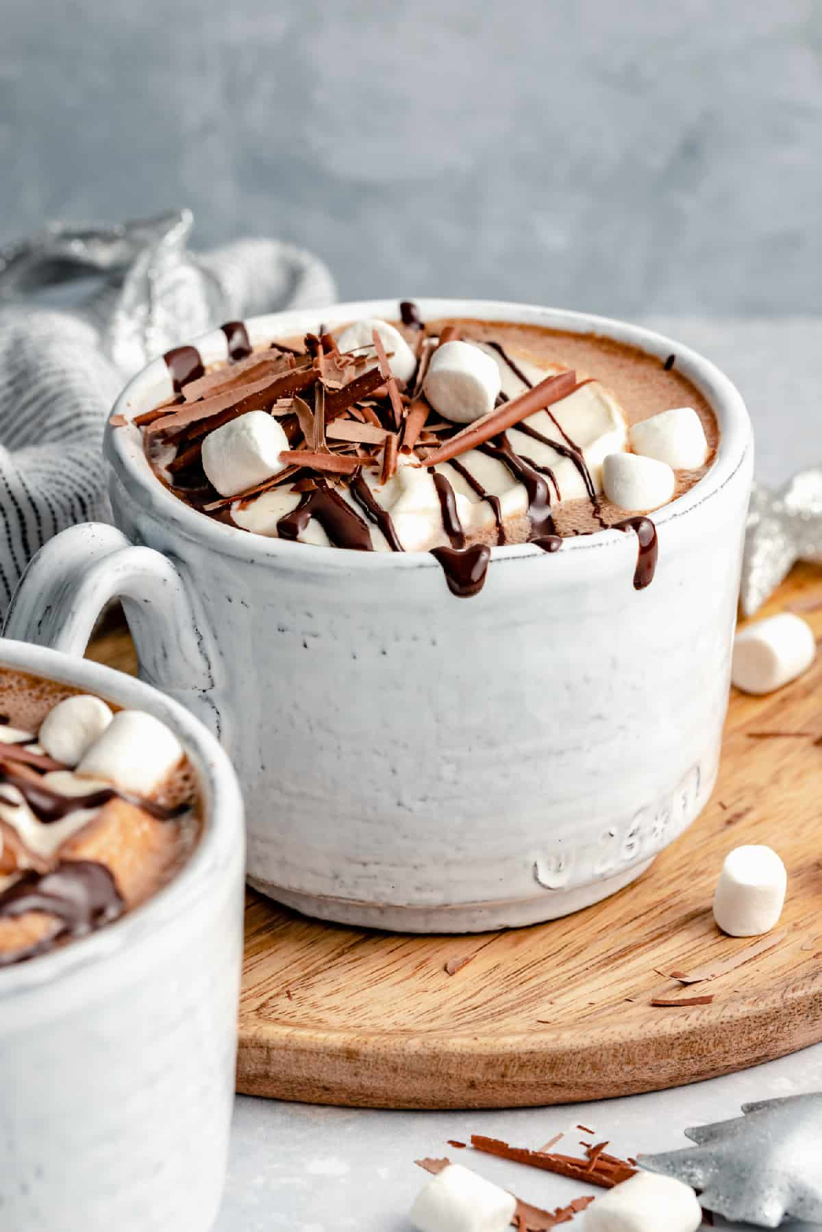 close up of a mug of frothy peppermint ganache hot chocolate topped with whipped cream, marshmallows and shaved chocolate, with melted chocolate dripping down the side of the mug