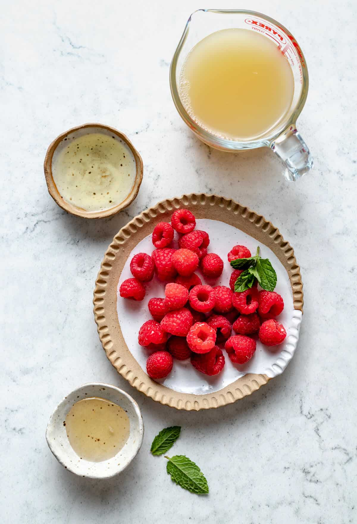 rapsberries, agave nectar, apple cider vinegar and apple juice in various jugs and bowls