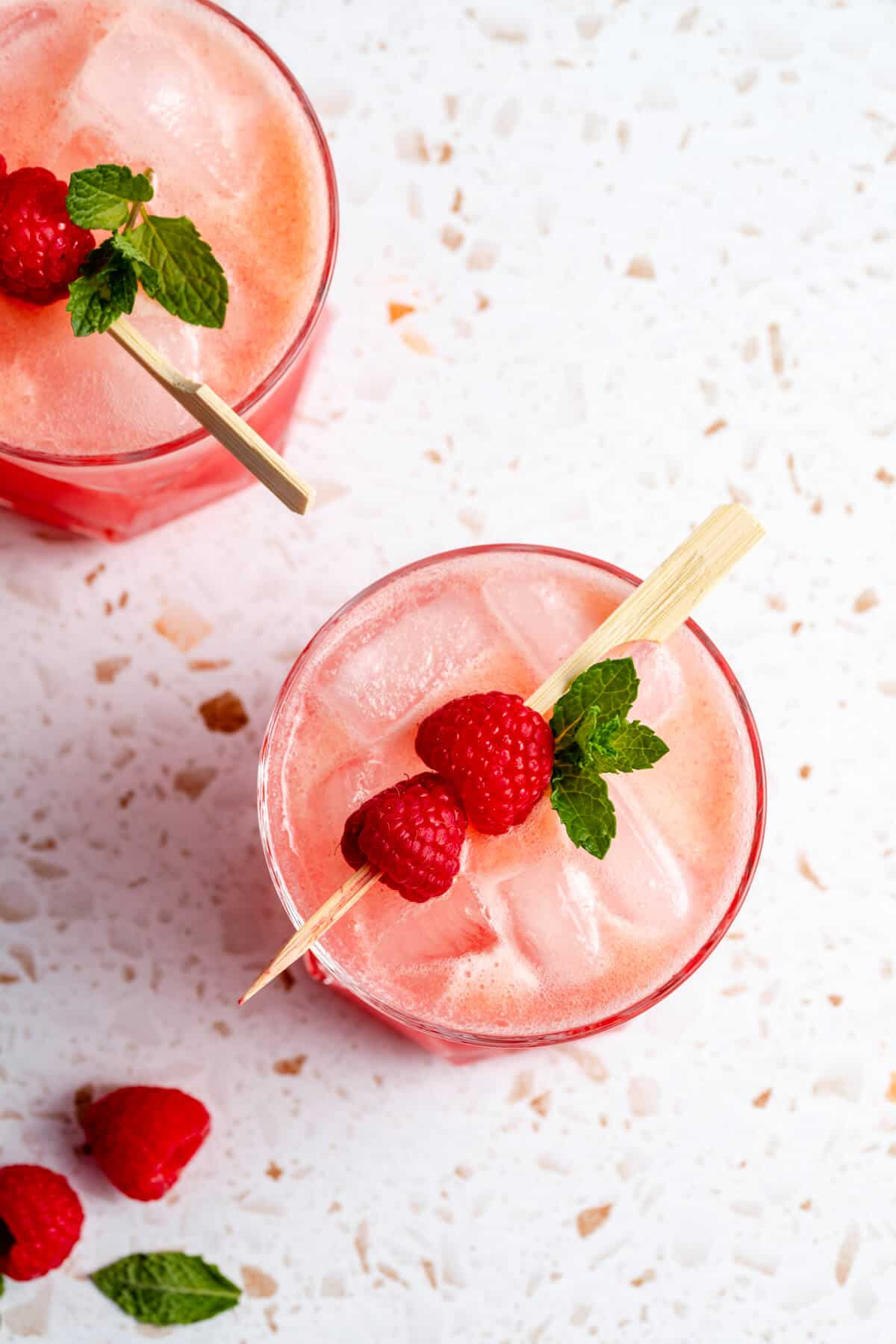 mocktail in a tumbler with ice floating on the top with raspberries on a skewer and mint leaves