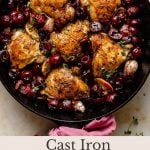 crispy chicken thighs in a skillet surrounded by juicy cherries
