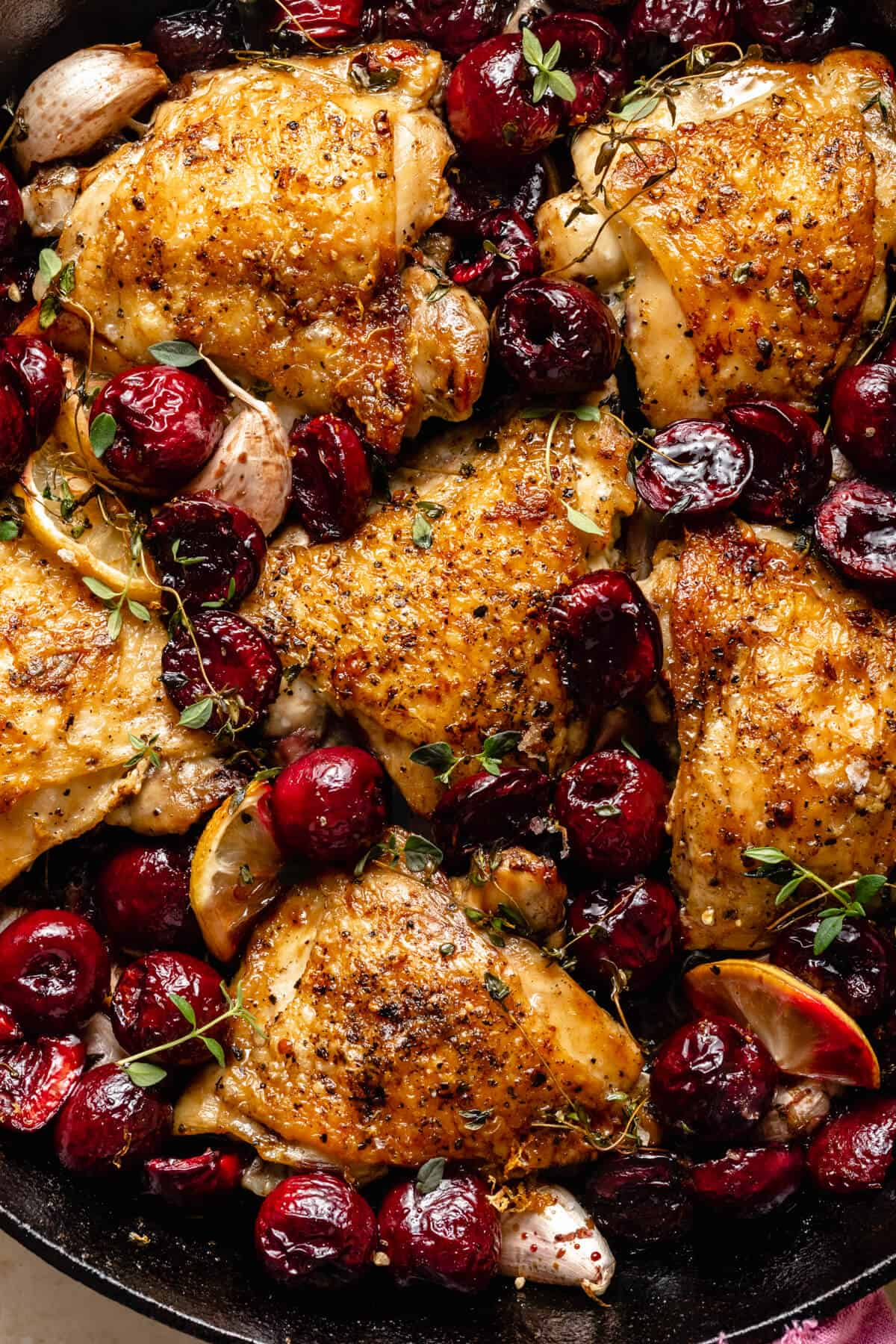 close up of crispy chicken skin and cherries surrounded with lemon slices thyme and garlic