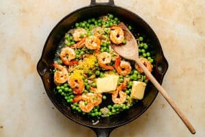 butter lemon zest and juice added to the shrimp mixture in a skillet