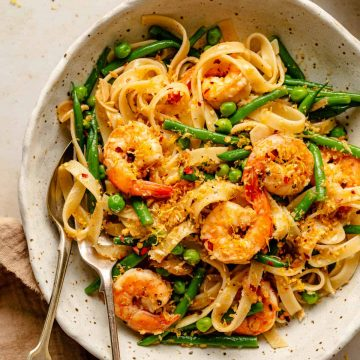 Bowl of pasta with shrimp, garlic and lemon with a spoon and fork
