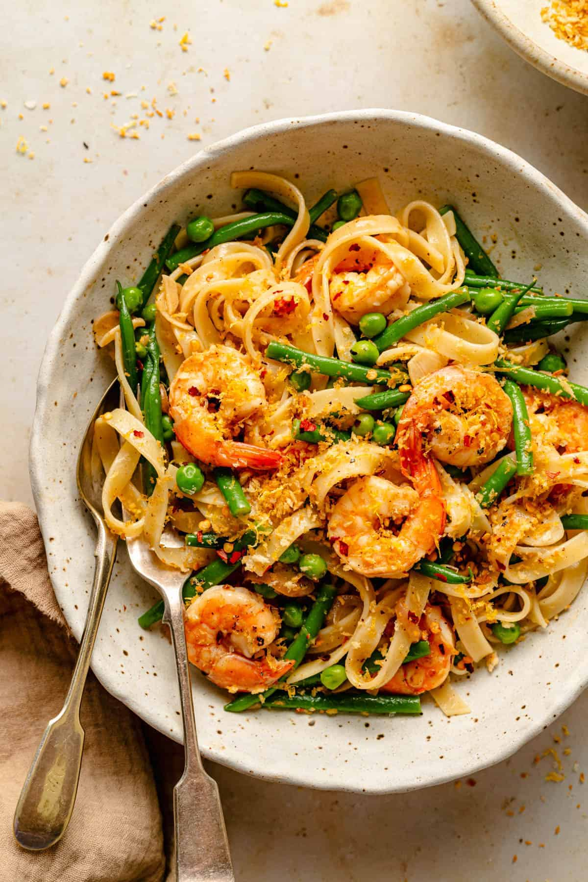 Lemon garlic and shrimp pasta in a bowl with pangrattato on top and spoon and fork