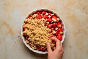crumble topping being sprinkled on top of the strawberries in a flan dish