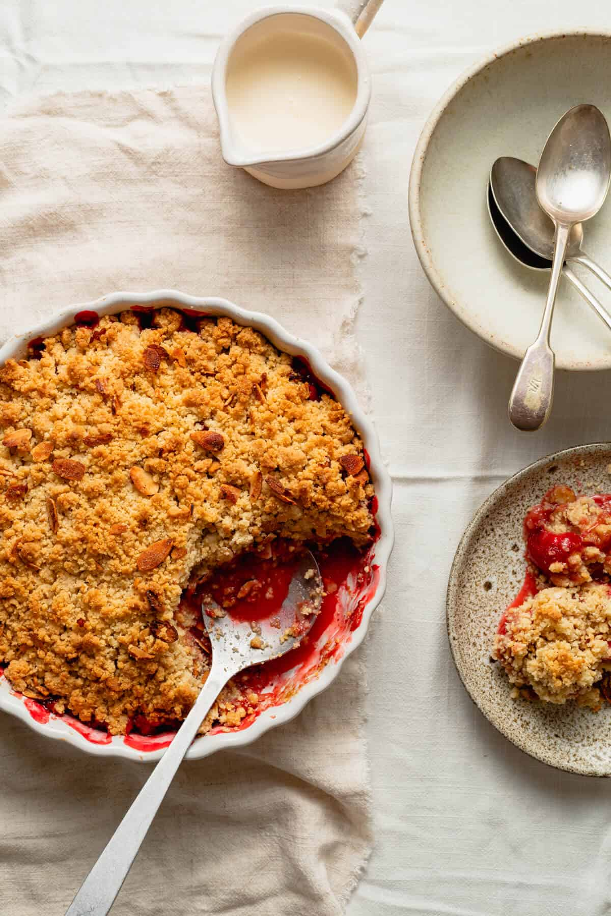 strawberry crumble baked in a flan dish and being served onto a plate with a spoon