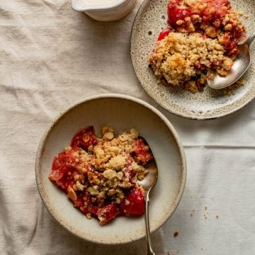 Strawberry crumble served up in a bowl and a plate with cream in a jug
