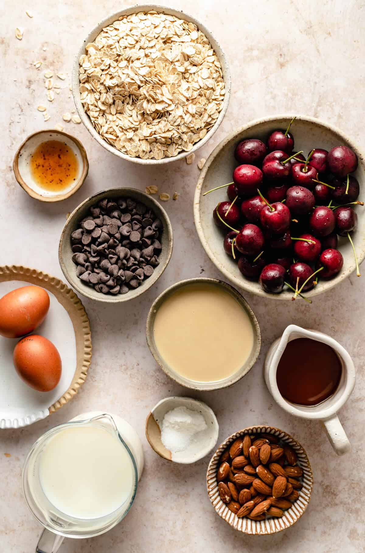 an array of bowls of ingredients including, cherries, chocolate chips, tahini, maple syrup, oats, eggs, milk and almonds