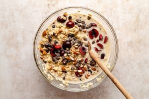 cherries almonds and chocolate chips stirred into wet oat mix with a spoon