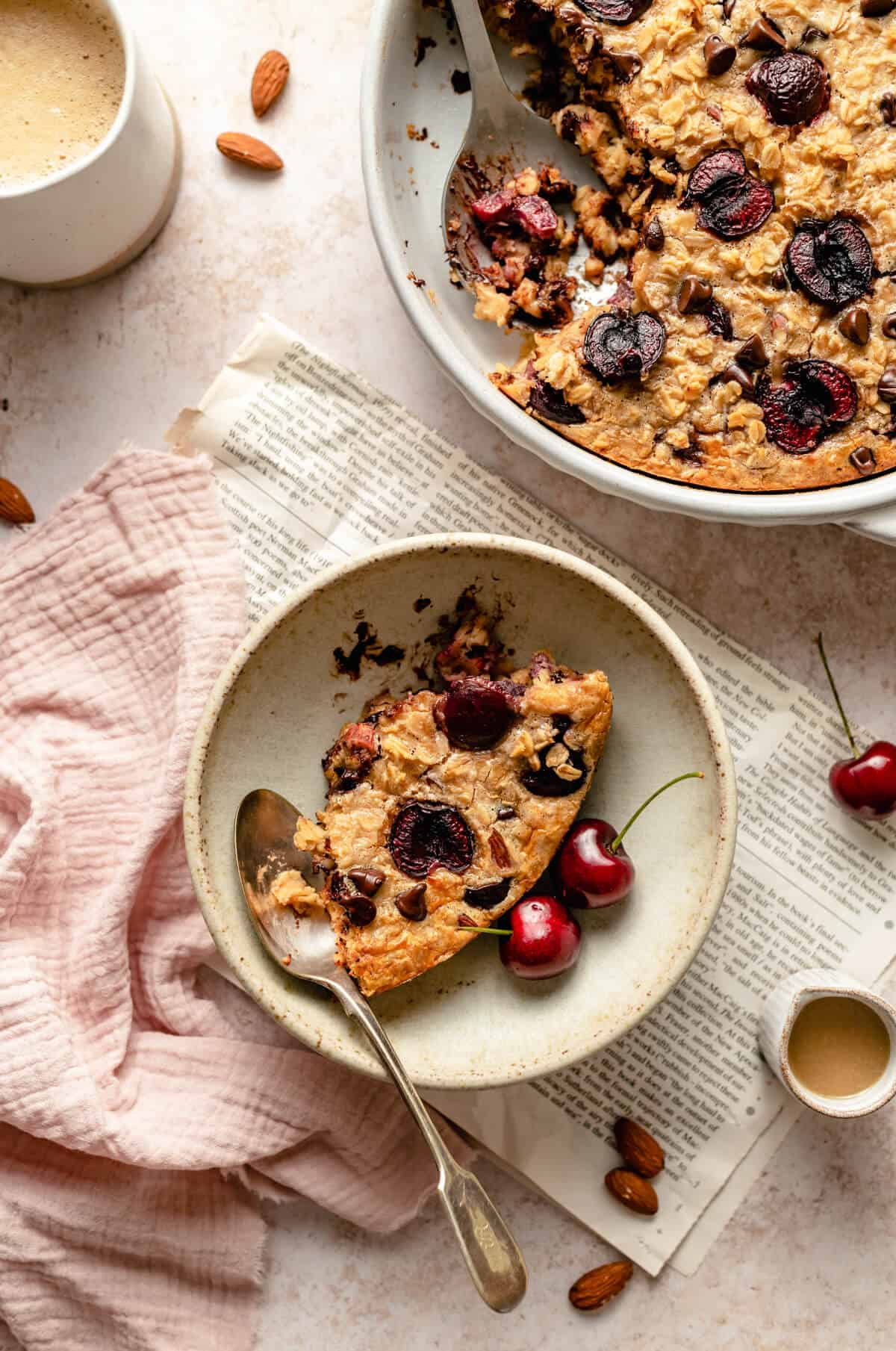 A serving of tahini cherry chocolate chip baked oatmeal in a bowl with a newspaper, cherries and a spoon