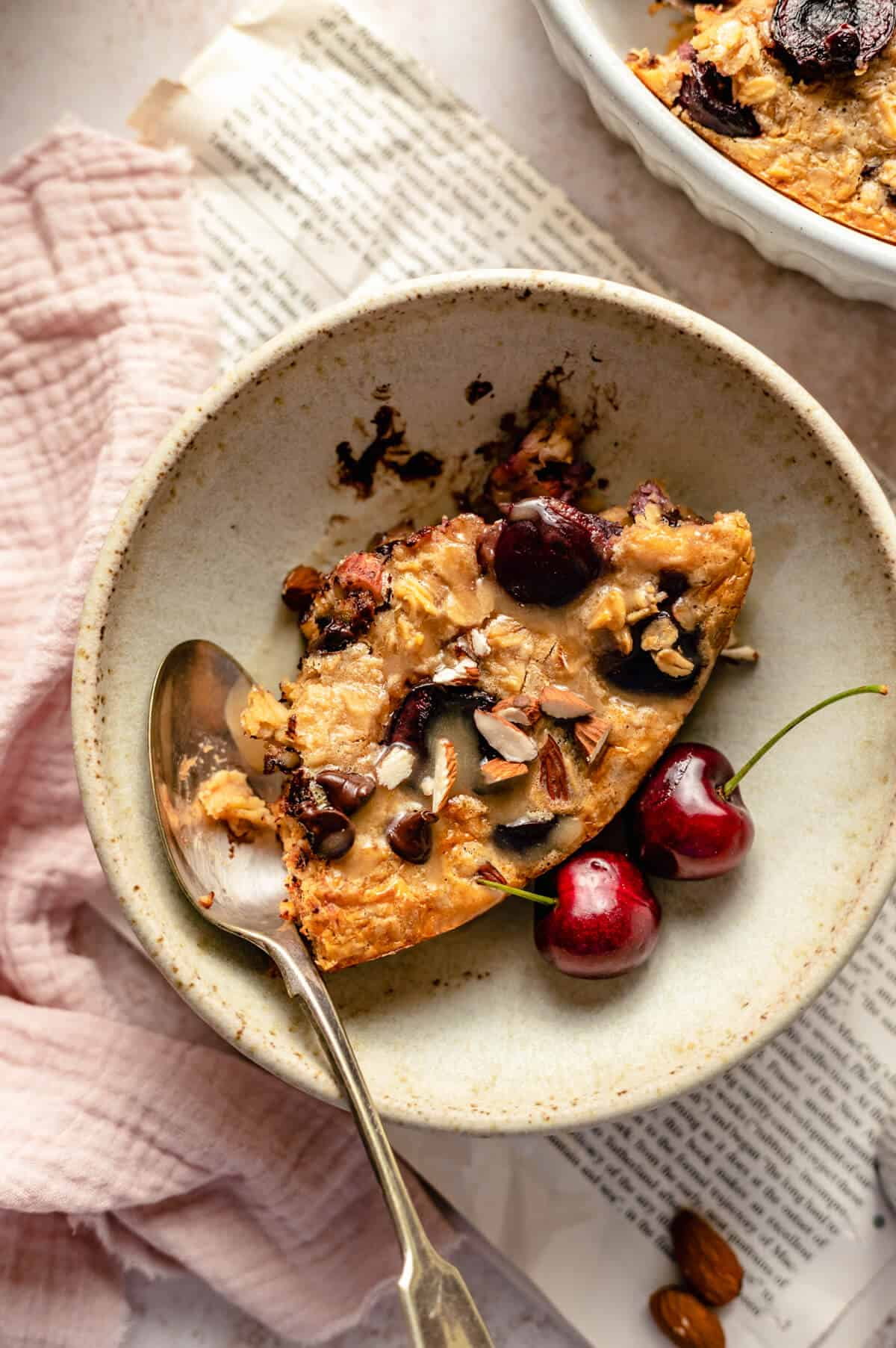 close up of the baked oatmeal in a bowl with a spoon, cherries and tahini drizzle on top.