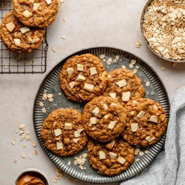 White chocolate chip oatmeal cookies on a plate with oats and biscoff in dishes to the side